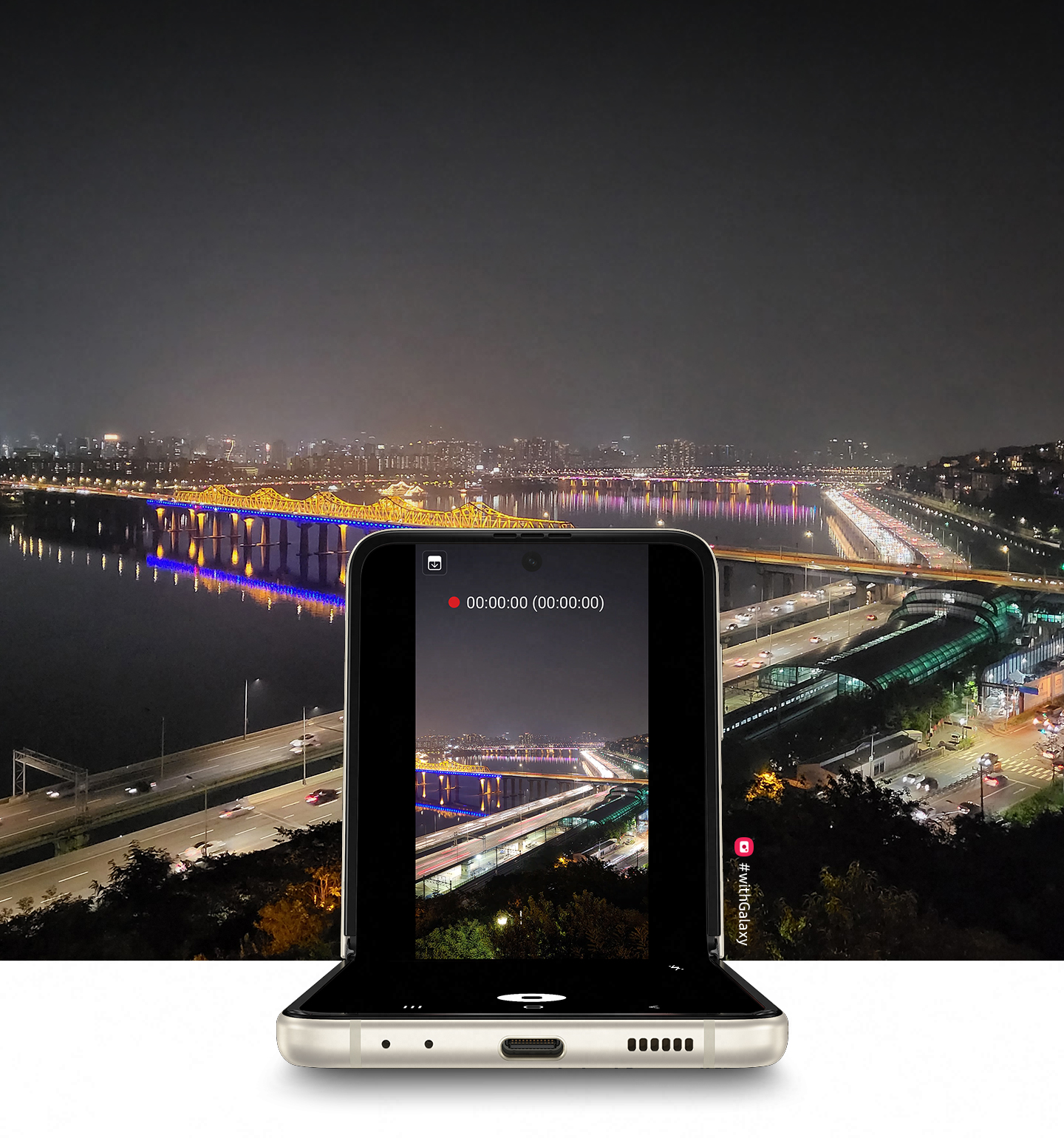 A view of a cityscape at night, as seen from the top of a hill. Galaxy Z Flip3 5G in Flex mode with the Camera app on the Main Screen and the same cityscape in the viewfinder, being recorded with Night Hyperlapse.