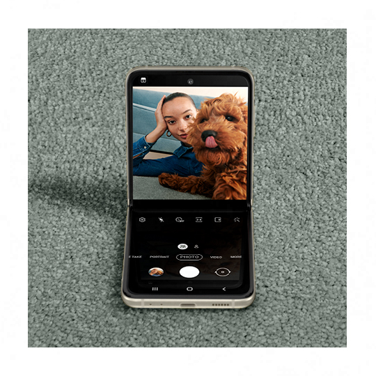 A woman taking a selfie with a puppy licking its nose. Galaxy Z Flip3 5G seen in Flex mode with the Camera app on the Main Screen, and the same photo seen in the viewfinder.
